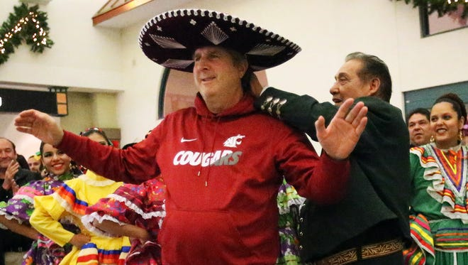 Washington State Cougars head coach Mike Leach gets help putting on a mariachi sombrero after the team's arrival at the El Paso airport Monday night.