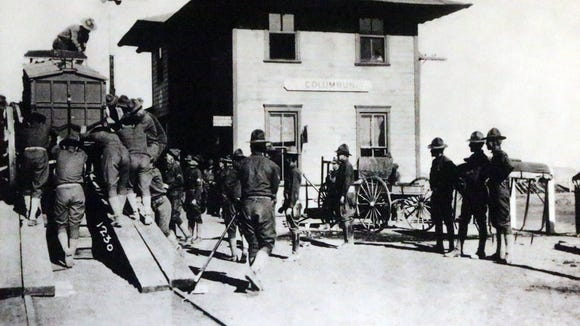 A photo of soldiers loading equipment onto a train