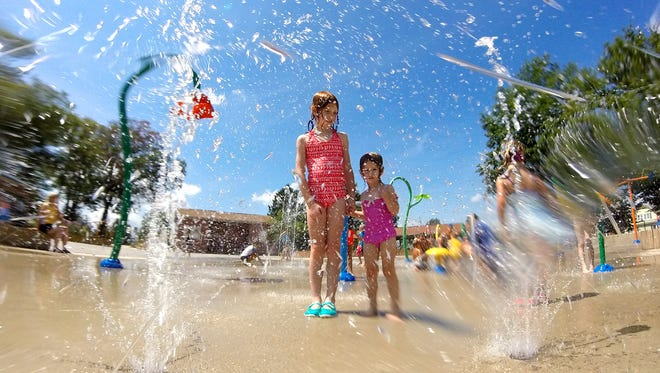 Clare Seifert, 8, left, and her sister Elise, 2, of Emigsville, stand in a spray of water at the Splash Pad in Red Lion, Friday, Aug. 12, 2016. John A. Pavoncello photo
