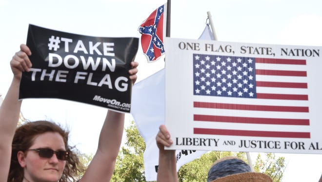 Two women hold posters against the Confederate flag during a protest rally in Columbia, S.C., June 20, 2015.