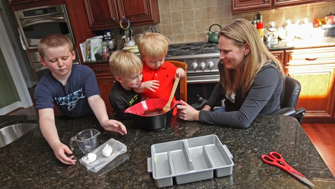 From left: Nine-year-old Wesley helps clean up ingredients while his brothers, 4-year-old Preston and 18-month-old Justin, stir brown mix together while baking with their mother, Caren Sydnor, Wednesday.