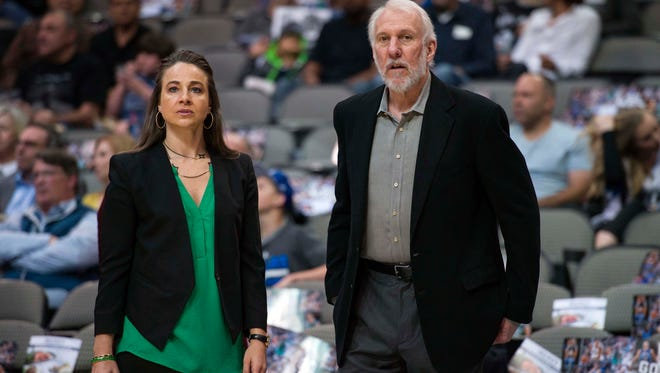 San Antonio Spurs assistant coach Becky Hammon and Spurs head coach Gregg Popovich watch their team warm up before a game against the Dallas Mavericks at the American Airlines Center.