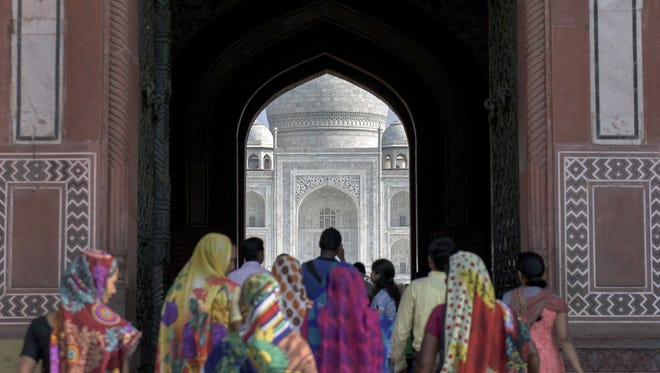 Indian tourists walk through a gateway at the entrance to the main mausoleum at the Taj Mahal complex in Agra.