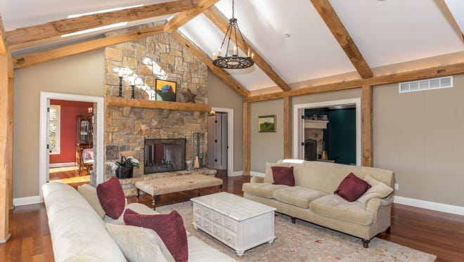 The right side of the great room has French doors leading into a library. On the other side of the two-sided natural stone fireplace is a formal dining room.