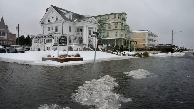 Ice forms as the winter storm mixed with high tide causes flooding on Beach Avenue in Cape May, N.J. Saturday.