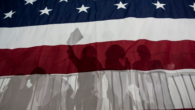 Democratic supporters are silhouetted in a large American flag at a rally following Super Tuesday on March 2, 2016 in New York City.