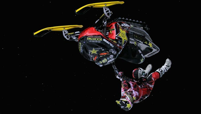 JANUARY 27:  Colten Moore kicks off the sled as he goes inverted doing a flip across a jump during the Snowmobile Freestyle elimination rounds at Winter X Games 15 on Buttermilk Mountain on January 27, 2011 in Aspen.