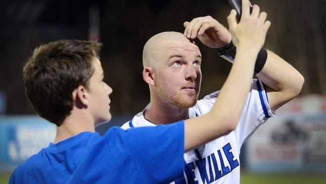 Sean Friedholm holds his cell phone up for his brother, UNCA baseball player Andrew Friedholm, to get a look at his newly shaved head at McCormick Field March 29, 2017. The UNCA baseball team shaved their heads to show their support for those fighting cancer.