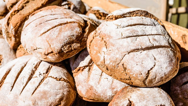 Pile with newly stone oven baked loafs of sourdough breads with lots of flour on top, lying outdoors in the sunshine in wooden crate.