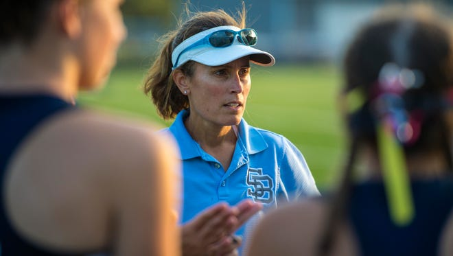 South Burlington field hockey coach Anjie Soucy meets with the referees and the captains and coaches from Mt. Mansfield before the start of their match in South Burlington on Wednesday, September 27, 2017.