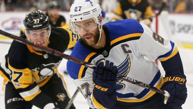 St. Louis Blues' Alex Pietrangelo looks for the puck along the boards as Pittsburgh Penguins' Carter Rowney (37) defends during the second period of the NHL preseason hockey game, Sunday, Sept. 24, 2017, in Cranberry, Pa. The preseason game was awarded to Rostraver Ice Garden, the winner of the 2016-2017 Kraft Hockeyville USA contest, but is being played at the UPMC Lemieux Sports Complex because Rostraver is not suitable for an NHL game. (AP Photo/Keith Srakocic)