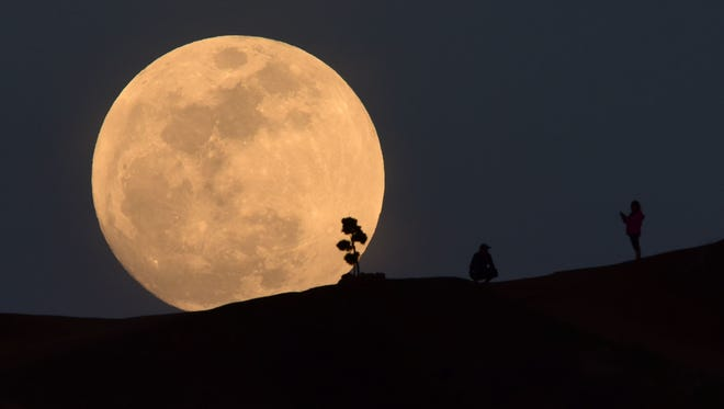 """TOPSHOT - A person poses for a photo as the moon rises over Griffith Park in Los Angeles, California, on January 30, 2018. Many parts of the globe may catch a glimpse on january 31 of a giant crimson moon, thanks to a rare lunar trifecta that combines a blue moon, a super moon and a total eclipse. The spectacle, which NASA has coined a """"super blue blood moon.""""   / AFP PHOTO / Robyn Beck        (Photo credit should read ROBYN BECK/AFP/Getty Images)"""