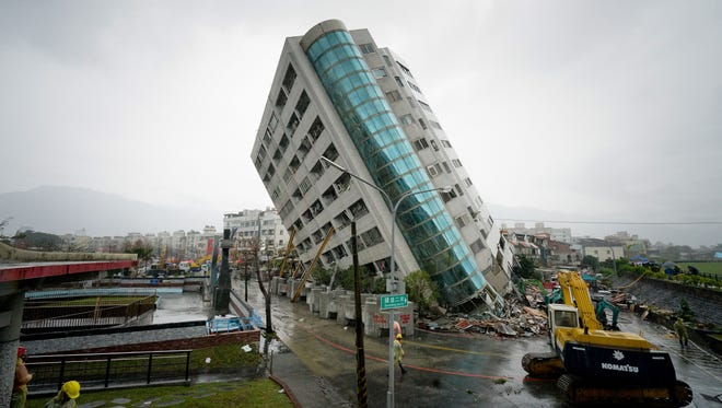 Rescue workers block off the area outside a building that tilted to one side after its foundation collapsed in Hualien, Taiwan.