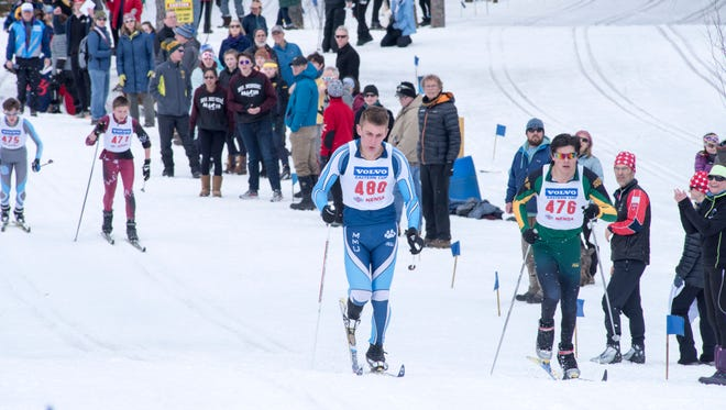 MMU's Max Eriksson, left, and BFA-St. Albans' Hazen Zada race during Monday's classical portion of the Nordic skiing high school state championships in Ripton.