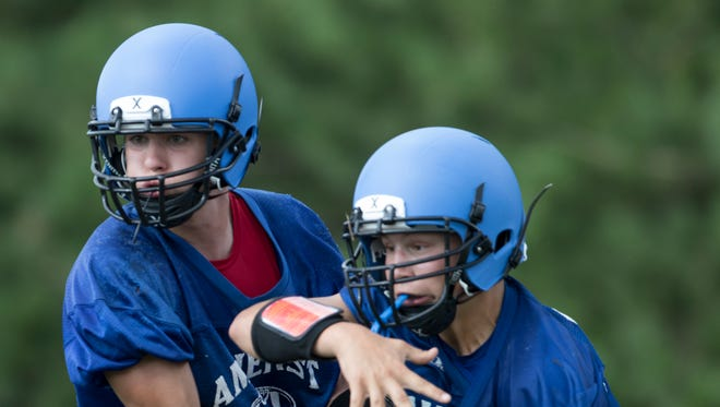Members of the Amherst football team run through a drill during practice earlier this month.