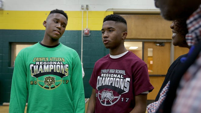 Crispus Attucks Tigers Micah Poole, left, and his brother Josiah Poole, a Tindley sophomore, listen to their father Mike Poole Tuesday, March 21, 2017, afternoon at Crispus Attucks High School. The Tigers are preparing for the 3A Indiana State finals game against the Twin Lakes Indians.