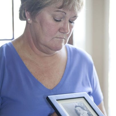 Cindy Harbin holds a photo of her father, Karl Dowd.