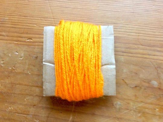 To make a yarn loop, wrap yarn around a cardboard square.