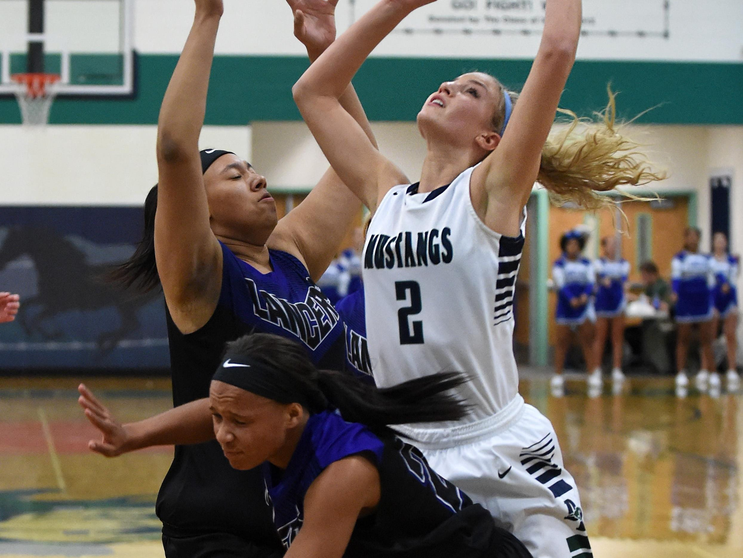 Damonte's Meagan Carlson pulls down the rebound against McQueen's Renesha Henderson, left, and Holly White, front, during Tuesday's game at Damonte Ranch High School.