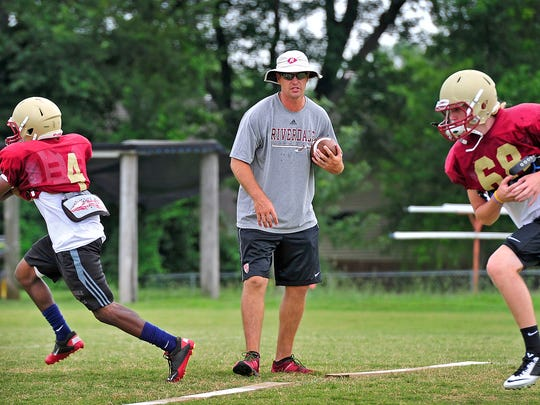 Former NFL quarterback Kelly Holcomb, center, coaches players during practice at Riverdale High School in Murfreesboro, Tenn., Wednesday, July 29, 2015.