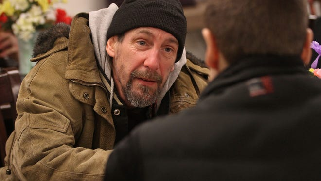 Brian Kulas talks with a homeless man, Stuart Bell, at Elijah's Promise during the 2014 Point in Time homeless census.