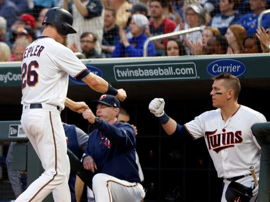 Minnesota Twins' Max Kepler, left, is congratulated by manager Paul Molitor and Logan Morrison, right, after scoring on a double by Eddie Rosario off Toronto Blue Jays pitcher Marco Estrada during the first inning of a baseball game Tuesday, May 1, 2018, in Minneapolis.