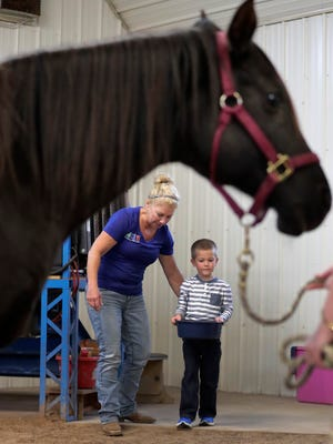 Lisa Kafka and Beckett Roerdink brings a bowl of treats to Maverick during a hippotherapy session at Exceptional Equestrians in De Pere, Wis.