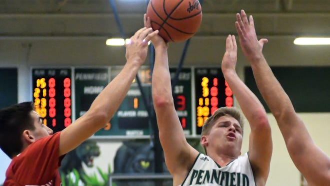 Pennfield's Grant Petersen (21) drives the basket between several Coldwater defenders Tuesday night.