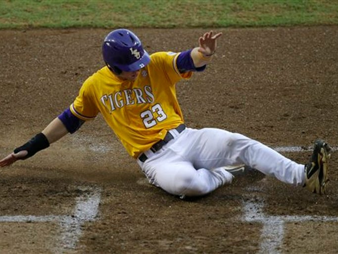 LSU's Jake Fraley (23) scores along with  Alex Bregman (8) on a  two-run RBI single Sean McMullen in the inning of an NCAA college baseball regional tournament game in Baton Rouge, La., Monday, June 2, 2014. (AP Photo/Gerald Herbert)