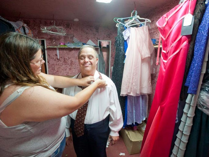 Volunteer Amanda Newton, of LaGrange, Ky., helps fix the tie of Apple Patch Community's Scott Shaheen backstage before the start of the Oldham County Fair Special Needs Pageant. 02 Aug 2014