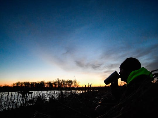 Jonathan Dixon drinks his morning coffee as the sun breaks over the horizon on a late season goose hunting trip off of J. Dance Road in eastern Henderson County Thursday, February 9 2017.