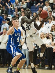 MMU's Deng Adiang (20) leaps for a lay-up against Colchester in a February game.