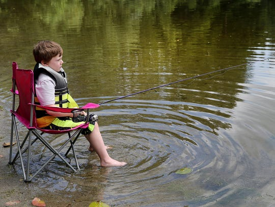 Greycen Riley, 7, of Bremerton, fishes for trout at