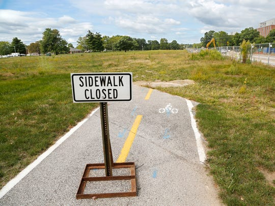 A sidewalk abruptly ends at a lot that was formerly