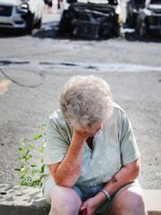 Florence Miller, of Eastpointe, lowers her head after arriving to pick up her family whose van burned in a parking lot at Beaubien and Gratiot in downtown Detroit while they were at a Tigers baseball game Sunday, July 19, 2015.