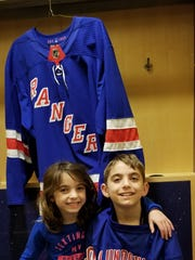 Brendan O'Callaghan and his sister, Caitlyn, sit outside Henrik Lundqvist's locker in Madison Square Garden, April 8,. 2018
