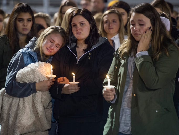 Students and community members gather for a candlelight