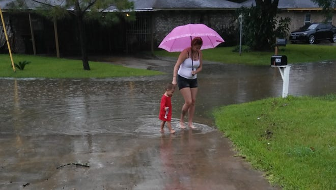 Michelle Navarro and her son, Jayden Jimenez, look at the flooding outside of their Houston home.