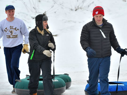 John Feemster, left, his sister Martha, both of Wausau, and Kyle Roth, of Madison, haul their snow tubes to be in line Friday, Dec. 26, 2014, at Sylvan Tubing Hill in Wausau.