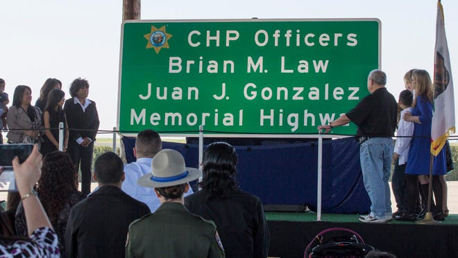 family members unveil a memorial highway sign during a ceremony for fallen CHP officers Brian Law, Clovis, and Juan Gonzalez, Tulare.