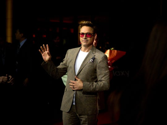 Robert Downey Jr. waves to fans at a red carpet event