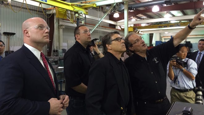 U.S. Senate candidate Matt Whitaker, left, and Texas Gov. Rick Perry, center, get a tour of at Master Tool & Mfg. Inc. in Hiawatha, Ia.
