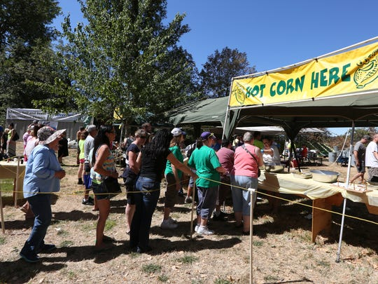 Festivalgoers wait in line for hot buttered corn on