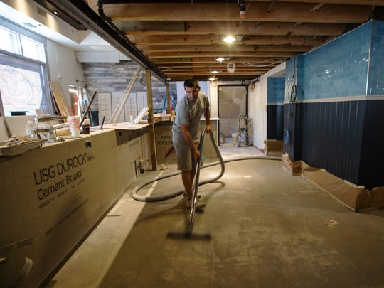 Andy Frields, 28, a worker for Concrete Solutions and Innovations, prepares the floor at Izzy's, a new seafood restaurant coming to downtown Fort Myers in the next few months.