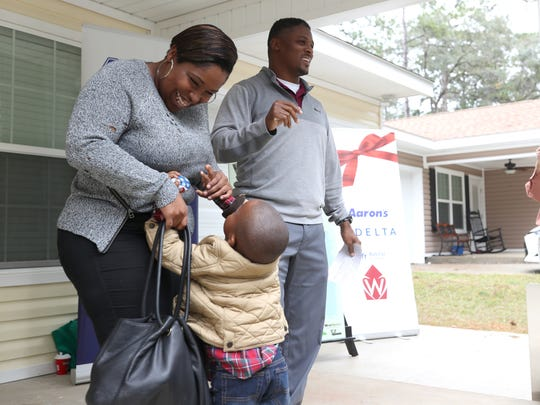 Warrick Dunn, surprises India Williams with a fully furnished home for her and her 3 children, twin 3-year-old boys Jeremiah and Joshua and 13-year-old daughter Asia on Wednesday. Williams was given the keys to her new home, which was built by Habitat for Humanity, along with the furnishings from Warrick Dunn Charity.