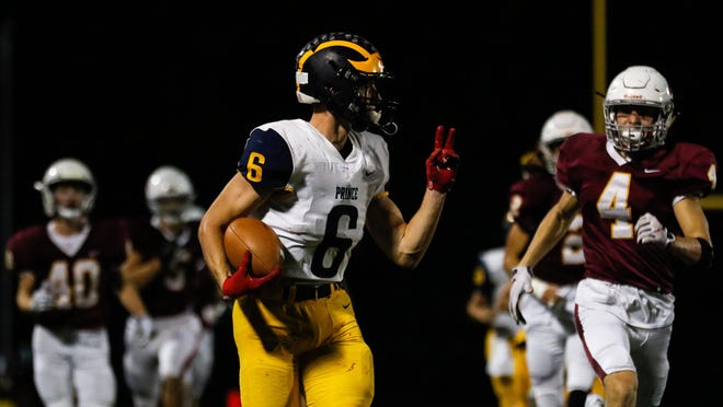 Prince Avenue's Landon Owens (6) throws a peace sign to the Holy Innocents' defense as he scores a touchdown off of a kickoff during the Wolverines' 35-25 win Friday night.