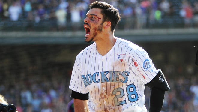 The Colorado Rockies' Nolan Arenado celebrates after hitting a walk-off three-run home run to complete the cycle during the ninth inning against the San Francisco Giants at Coors Field.