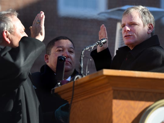 Judge Stephen Linebaugh, left, swears in York Mayor Michael Helfrich during his inauguration outside of City Hall on Tuesday. Latino community organizer Lou Rivera, center, holds the Bible for the ceremony.