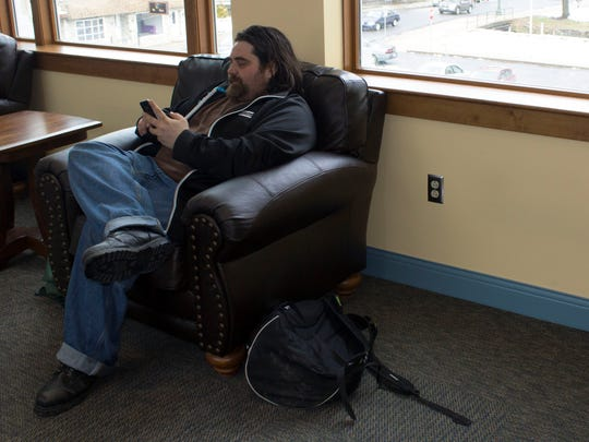 Jason Davies, 34, sits on a chair and plays on his cell phone at the Coyle Free Library in Chambersburg the morning of Monday, April 2. Davies said he has been chronically homeless most of his adult life, and will often go to the library to use their internet and read some books.