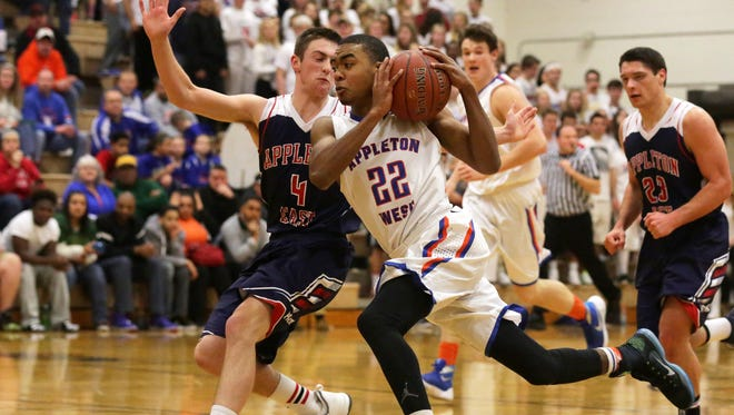 Pierre Majors of Appleton West drives to the basket while being guarded by Nathan Brice of Appleton East during a Fox Valley Association basketball game Friday at West.